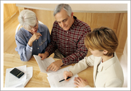 Home alarm company rep and customers reviewing paperwork